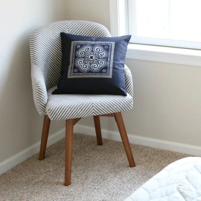 west-elm-chair-with-ten-thousand-villages-blue-decorative-pillow-with-bed-corner-square