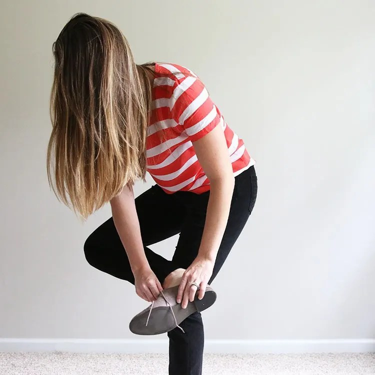 woman in orange and white striped shirt putting on shoes