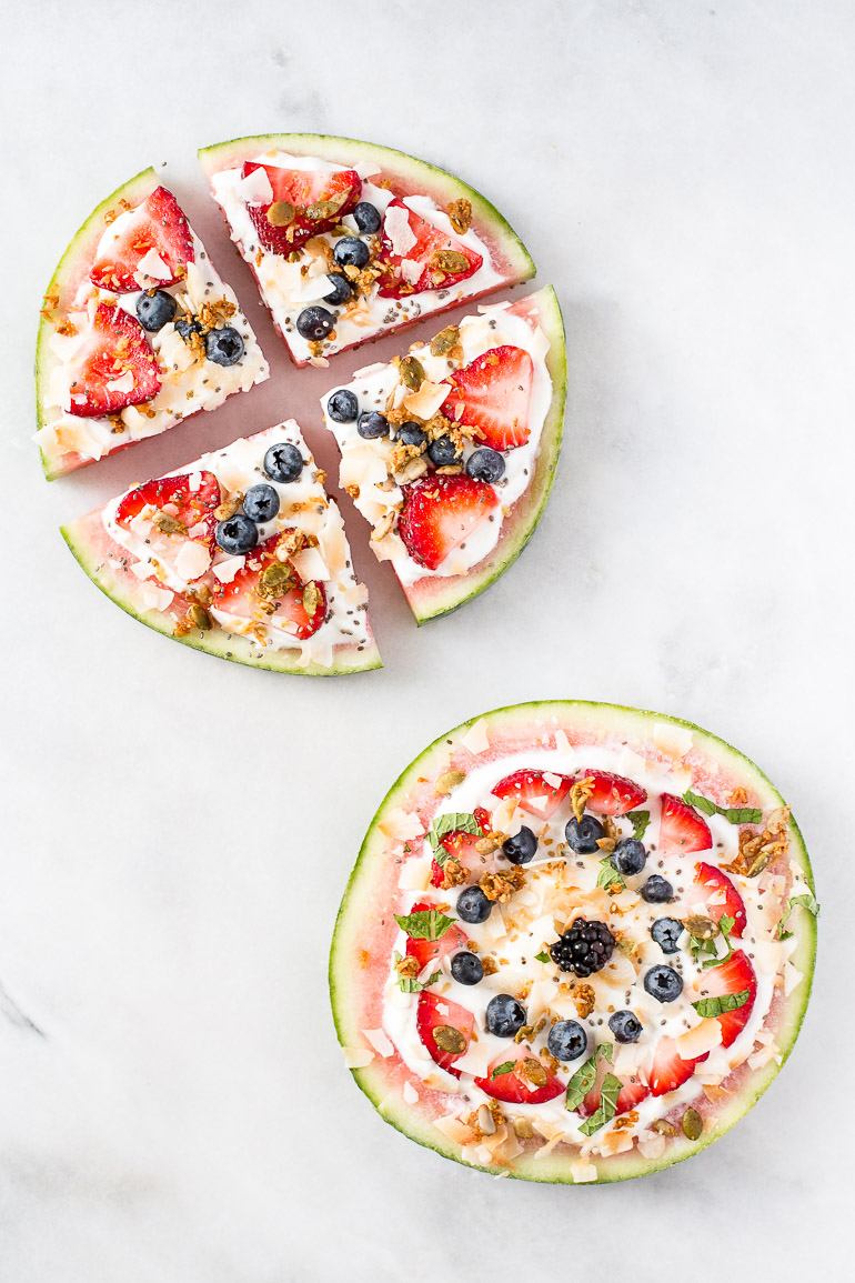 A refreshing summertime snack using sliced watermelon topped with coconut yogurt, toasted coconut flakes, fresh berries, chia seeds, and crunchy granola. Perfect for picnics and barbecues! | vegan + paleo + sugar free + raw option | via Honestly Nourished