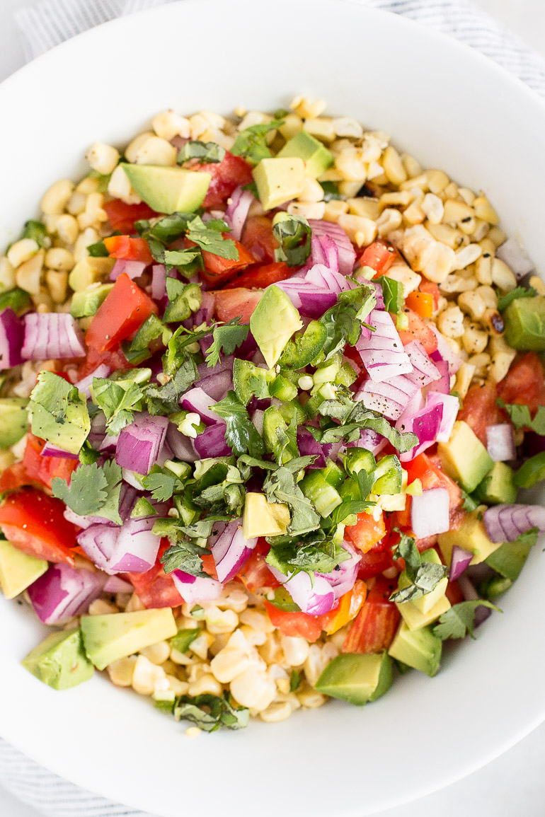 A fresh, no frills recipe for grilled corn and heirloom tomato salad with chili lime vinaigrette that highlights seasonal summer produce at its best. Simply toss the corn on the grill for 10-15 minutes and add veggies and a protein of your choice for a lightening quick lazy summer dinner! | GF + DF + vegan + paleo-ish