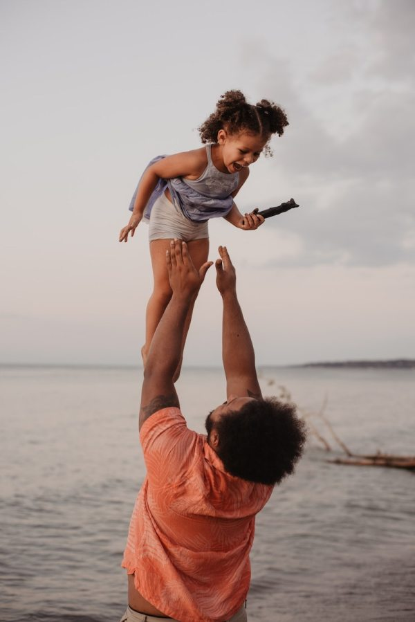 Black Father and daughter enjoying vacation photo at the beach