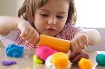 girl-toddler-rolling-playdoh
