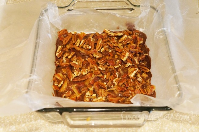 lined baking dish with melted chocolate, pecans and bacon
