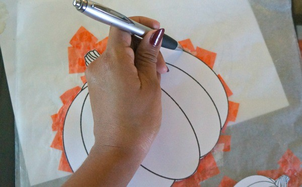 Making pumpkin suncatchers, tracing pumpkin stencil to be cut out
