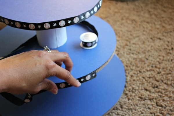 How to Make a DIY Cupcake Stand, glue ribbon around the exposed edges of each card board cake round tier