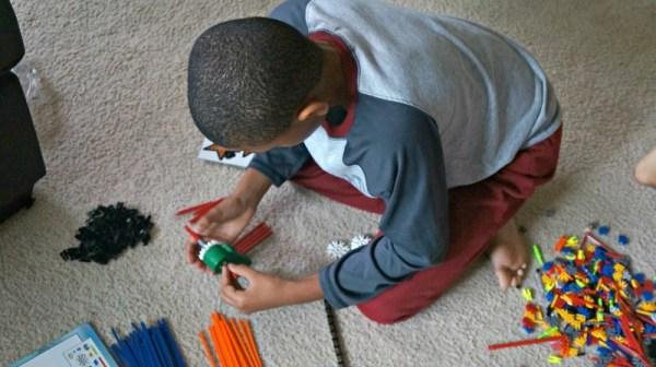 Holiday STEM gifts, boy builds the K'NEX roller coaster