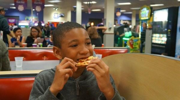 Kid eats pizza at Chuck E Cheese's