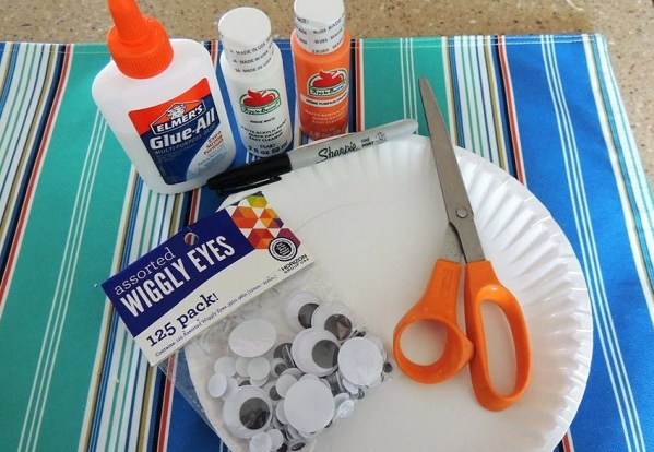Materials needed to make a tropical clown fish paper plate fish craft for kids