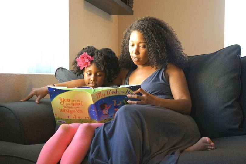 African American mother and daughter reading together