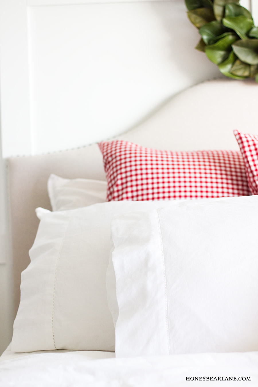 white and red pillows on bed - Honeybear Lane