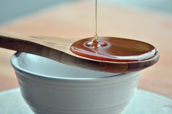 Honey dripping into a wooden spoon. Glucose oxidase plays a major role in honey's antimicrobial action.
