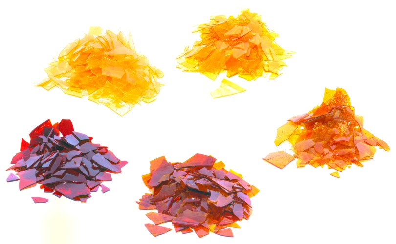The resin produced by lac bugs is purified and sold as dry flakes in different colors. Public domain photo by Nuberger13