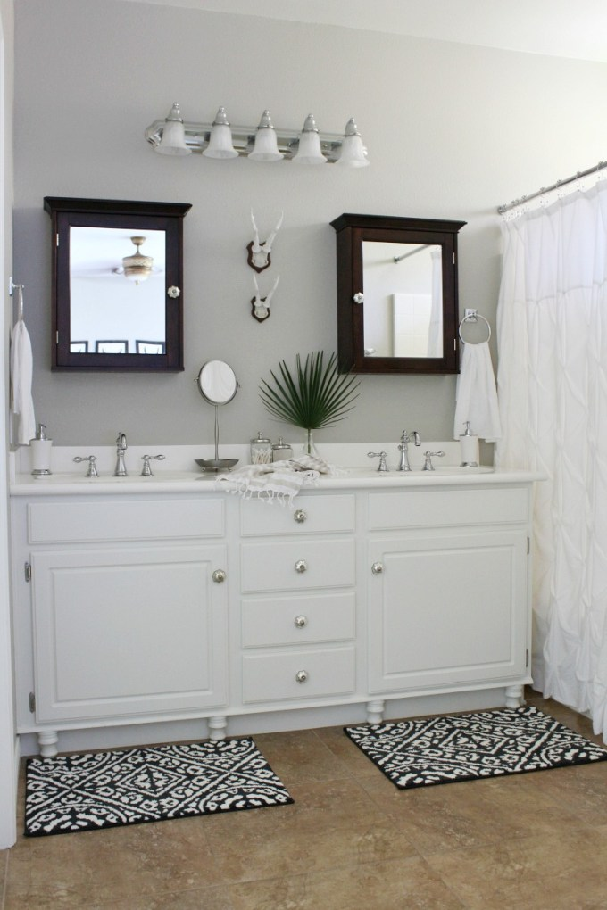 Builder's grade master bathroom makeover on a budget, add wood feet to a bathroom vanity, fix swollen MDF cabinet doors, fan leaf palm, patterned tile rug