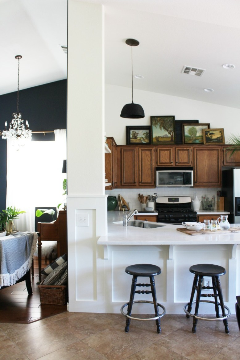 art in the kitchen, vaulted ceiling, dark walls, wood cabinets