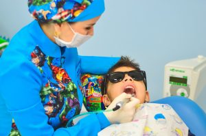 Look how cool that dentist is, with all those comic book characters on her and shades for the kid? So cool. COOL.