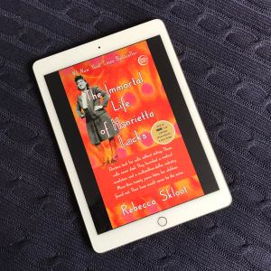 """An iPad showing the cover image of """"The Immortal Life of Henrietta Lacks"""" by Rebecca Skloot lays on a navy blue throw blanket"""