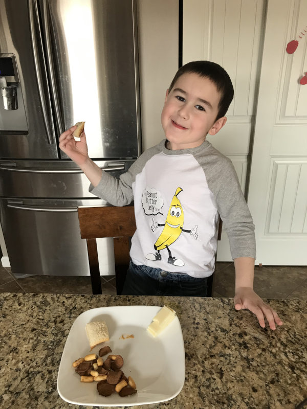 """A young boy eats a peanut butter and jelly sandwich wearing a raglan shirt featuring a cartoon banana wearing white gloves and gray sneakers with a speech bubble that reads: """"It's peanut butter jelly time."""""""