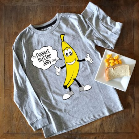 """A gray long sleeve shirt with a cartoon banana wearing white gloves and grey sneakers shows a speech bubble that reads: """"It's Peanut Butter Jelly Time."""" The shirt lays on a wooden table with a small plate of a half-sized peanut butter and jelly sandwich and a few goldfish crackers."""