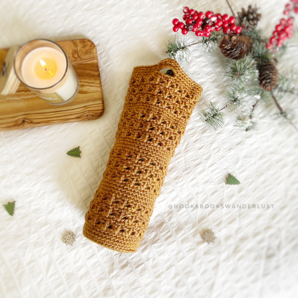 Gold colored Merry + Bright Wine sleeve lays on a white background with a candle burning on a piece of wood next to it and the top of a wine bottle peeking out, and greenery and red berries with pinecones off to the side.