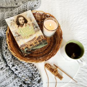 """A light brown, shallow, round wicker basket lays on a white background with a cup of tea, a gray shawl, and a small swatch of gold crochet with a wooden hook arranged around it holds a paperback copy of the title """"Pont Neuf"""" by Max Byrd and a white candle."""