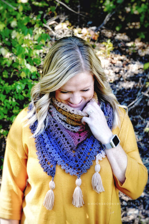 A blonde woman reaches for the neck of her autumn walks triangle scarf