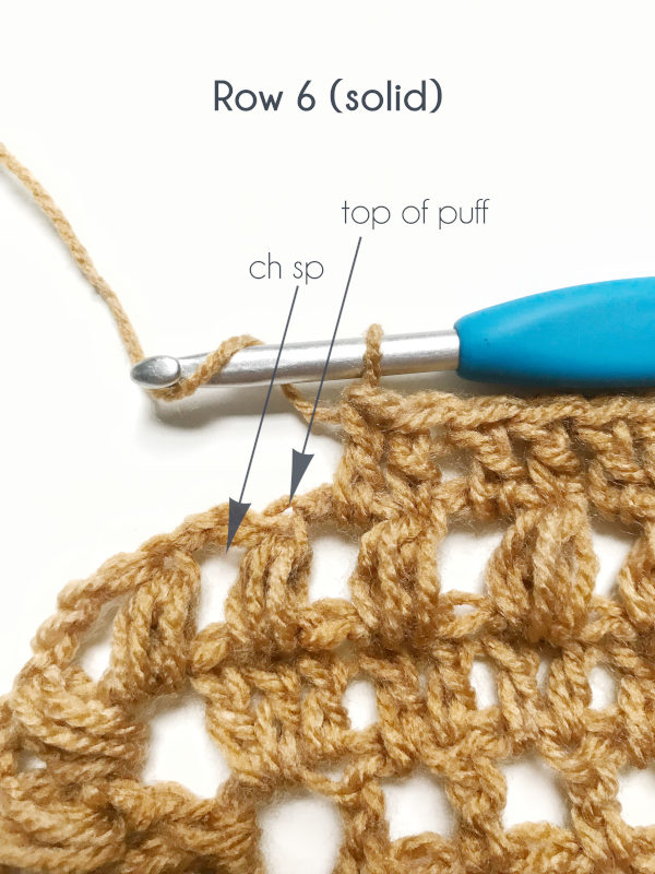 Arrows point to the top of the puff stitch and to the chain space where double crochets are to be worked.