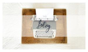 """An antique typewriter with a piece of paper bearing the Hooks, Books, & Wanderlust logo at the top coming out of it is arranged on a rustic drafting board with the words """"Travel & Lifestyle"""" in dark blue across an opaque white banner."""