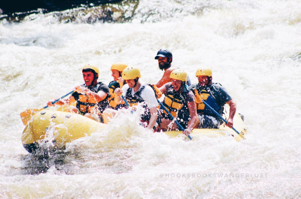 A group of 6 people are white water rafting