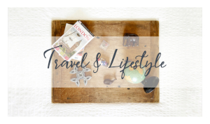 """Travel mementos and books are arranged on a rustic drafting board with the words """"Travel & Lifestyle"""" in dark blue across an opaque white banner."""