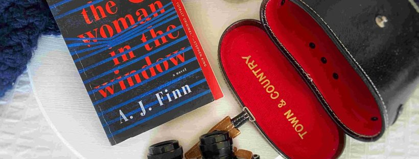 "A round white wooden tray is set with a lit candle, a pair of binoculars and their open black leather case with red velvet lining are visible next to a paperback copy of the book ""The Woman in the Window"" with a navy blue throw in the top half of the picture."