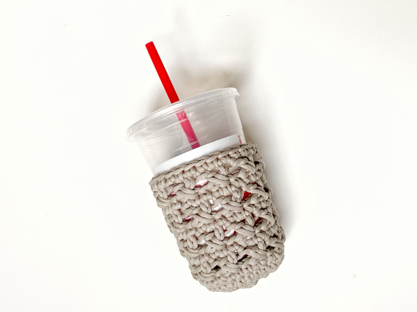 A taupe-colored XOXO Cold Cup Cozy lays completed on a white background with an empty smoothie cup with a red straw inside it.