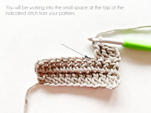 """A swatch of double crochet in taupe color shows a hook holding a working loop after making three double crochets in the row. An arrow points to the small space under the top 'v' of the next stitch. Text on the photo reads: """"You will be working into the small space at the top of the indicated stitch from your pattern."""""""