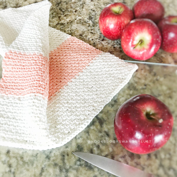A cream colored handmade kitchen towel with a coral colored stripe lays on a granite countertop with a glass cutting board, knife, and a scattering of 5 red gala apples.