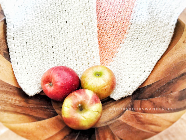 A cream colored handmade kitchen towel with a coral colored stripe lays draped over a teak wooden bowl that contains 3 red and gold gala apples.