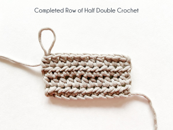 """""""Completed Row of Half Double Crochet"""" Photo shows a taupe colored swatch of four rows of half double crochet on a white background."""