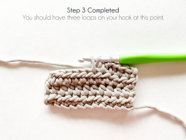 """""""Step 3 Completed: You should have three loops on your hook at this point."""" Photo shows a semi-formed 5th half double crochet stitch in the 4th row of a taupe swatch of yarn, where a loop was just pulled up through the stitch and counts 3 working loops on the hook."""