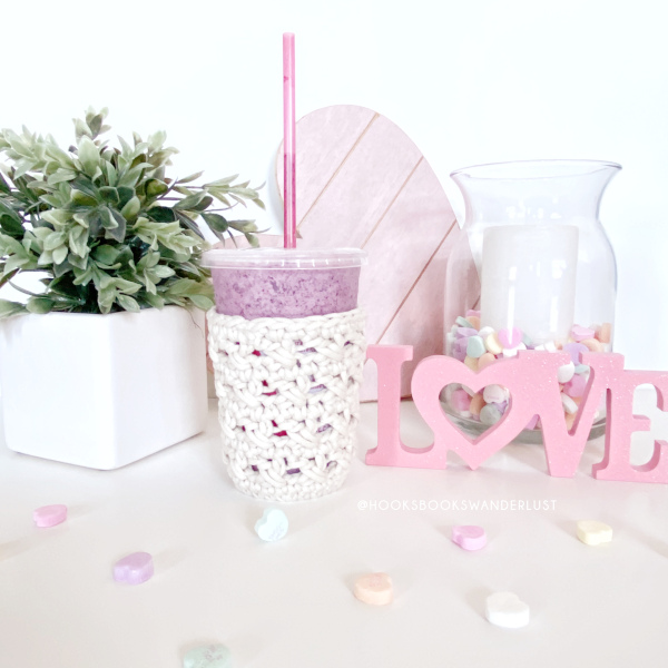 "A white XOXO Cold Cup Cozy holds a cup of a purple smoothie in the center of the photo, a pink wooden heart sign laying on its side behind it, a glass hurricane candle holder filled with candy hearts and a white candle sitting just to the right of the wooden heart, a laser cut pink sign sits in front of the candle holder to the right side of the cup and reads ""LOVE,"" and a potted plant in a white cubic planter appear to the left of the cup and candy hearts have been sprinkled all around."