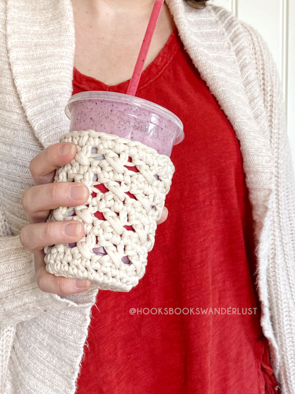 A woman wearing a read shirt under a cream sweater cardigan holds a white XOXO Cold Cup Cozy containing a cup of a purple smoothie.