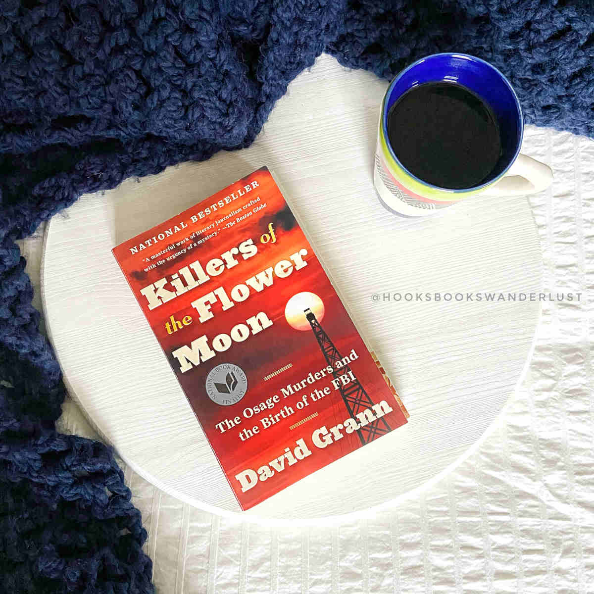 """A mug of steaming tea sits next to a paperback copy of """"Killers of the Flower Moon"""" on a white wood round which is surrounded by a navy blue crochet blanket."""