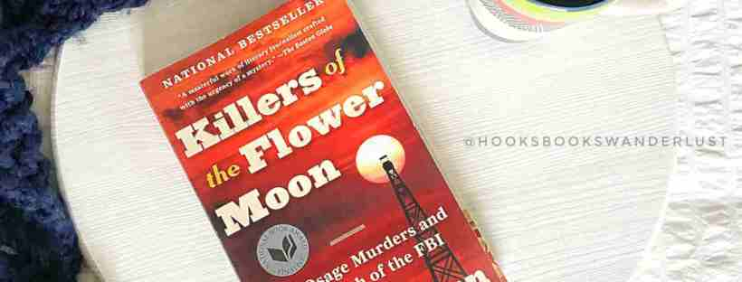 "A mug of steaming tea sits next to a paperback copy of ""Killers of the Flower Moon"" on a white wood round which is surrounded by a navy blue crochet blanket."