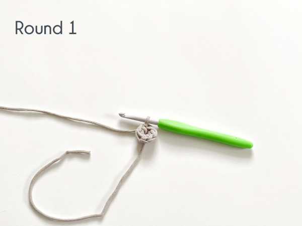 """One round of single crochet has been worked in flat circle in a taupe colored cotton yarn laying on a white background. Text on the photo reads: """"Round 1."""""""