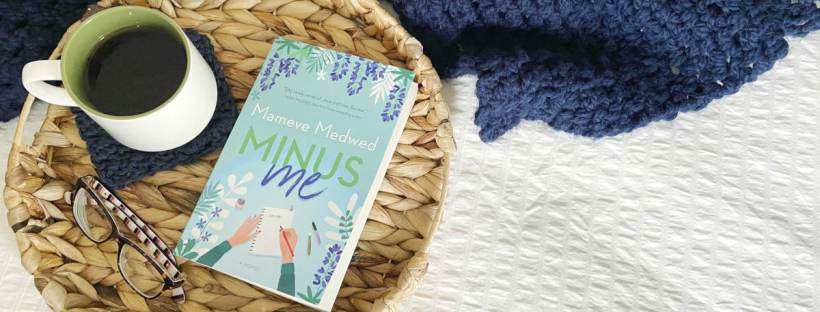"A quality paperback copy of the book titled ""Minus Me"" by Mameve Medwed sits next to a white mug with a green interior full of steaming tea resting on a navy blue crocheted coaster and a pair of tortoise shell glasses on a wicker tray resting on a white background surrounded by a navy blue crocheted throw blanket."