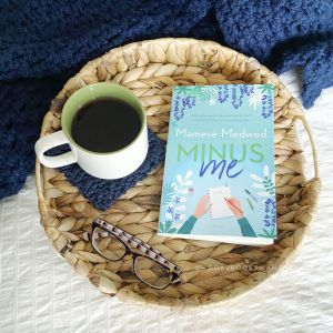 """A quality paperback copy of the book titled """"Minus Me"""" by Mameve Medwed sits next to a white mug with a green interior full of steaming tea resting on a navy blue crocheted coaster and a pair of tortoise shell glasses on a wicker tray resting on a white background surrounded by a navy blue crocheted throw blanket."""