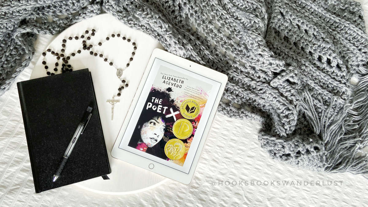 """An iPad with a photo of the cover image of """"The Poet X"""" lays next to a black hardcover journal, black pen, and black beaded rosary on a white wood tray laying on a white background with a gray wrap spread out around it."""