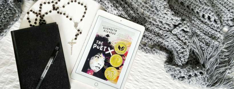 "An iPad with a photo of the cover image of ""The Poet X"" lays next to a black hardcover journal, black pen, and black beaded rosary on a white wood tray laying on a white background with a gray wrap spread out around it."