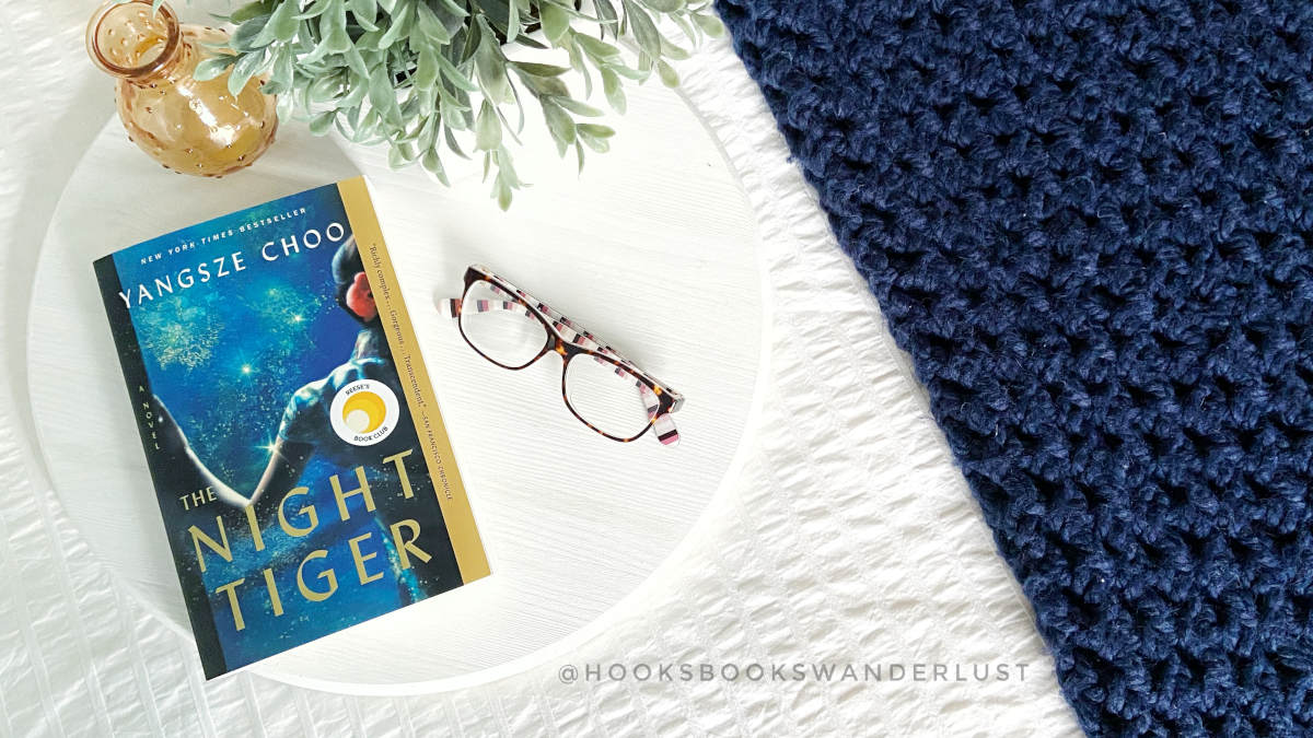 """A paperback copy of the novel """"The Night Tiger"""" by Yangsze Choo sits on a white tray with an amber colored vase, some faux greenery, and a pair of glasses. The tray sits on a white bedspread next to a navy blue throw blanket."""