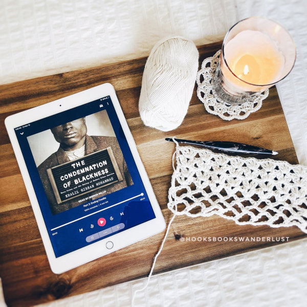 "An iPad showing the cover image of an audiobook titled ""The Condemnation of Blackness"" by Khalil Gibran Muhammad lays next to a working crochet project, a ball of cream yarn, and a candle lay on a wooden board on top of a white bedspread."