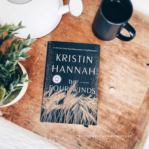 """A hardback copy of the book """"The Four Winds"""" by Kristin Hannah sits on a wooden drafting board next to a white metal watering can, a green and white on terra cotta vase holding faux greenery, and a black mug of hot tea."""