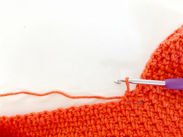 Image shows the first stitch of the new side skipped, a chain stitch, and a single crochet worked into the chain-1 space of the new side.
