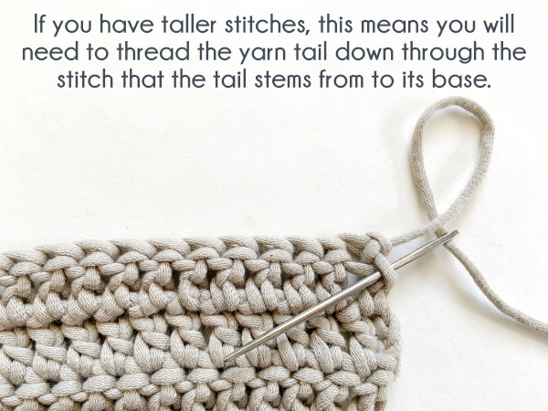 """Image shows the needle inserted into the post of the last stitch, working down the post to reach the bottom of the stitch. Text reads: """"If you have taller stitches, this means you will need to thread the yarn tail down through the stitch that the tail stems from to its base."""""""